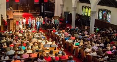 A capella group performing for audience in Herrick Chapel