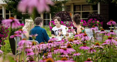 Students framed by the flowers surrounding their outdoor seating area
