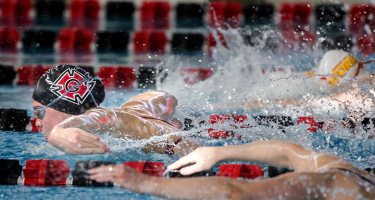 Woman swimming in Grinnell swim cap takes the lead