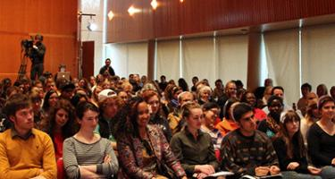 Speaker in Rosenfield Center Room 101 talks to packed crowd