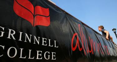 Large scarlet and black Grinnell College Alumni banner with man leaning back against the wall it is one