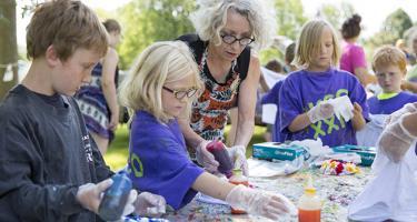 Tilly Woodward helps children create art in an outdoor outreach program