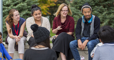 Students and staff in a discussion circle
