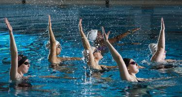 Six swimmers performing a sychronized routine in a pool