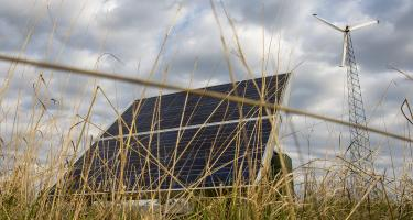 Solar panel in prairie with a wind turbine in background