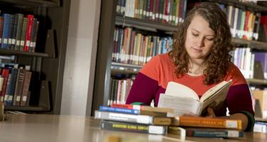 Emily Ricker reads a book in the library