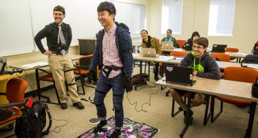 Student wearing motion capture suit plays Dance Dance Revolution while lauging classmates and professor look on