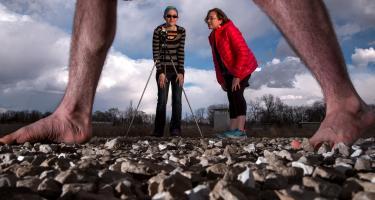 Rachel Sutter '20 behind camera captures gait of test subject walking on gravel while Liz Queatham looks on.