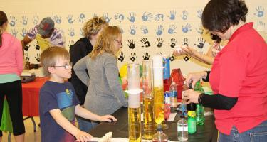 A boy watches a set of large beakers during a public chemistry demonstration.