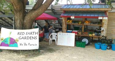 """Red Earth Gardens """"We be farmin'"""" sign next to display of produce"""