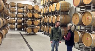 Ben Hoekstra and Doug Wood in warehouse filled with wooden barrels