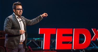 Lester Aleman speech beside large TEDx logo