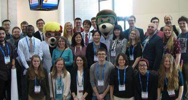 The group of 28 have conference name tags on and pose with two people dressed up in mole costumes complete with lab coats and safety goggles.