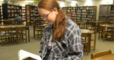 Katrina Sieck reading a book in the Grinnell HS Library