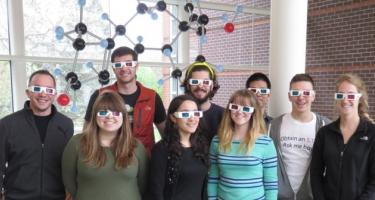 Students in the Advanced Inorganic Chemistry class wear 3D glasses and pose in front of a large chemical structure.