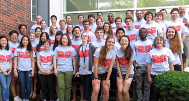 Chemistry summer research students and their faculty mentors pose in student-designed t-shirts in the Noyce Science Center courtyard.