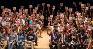 117 students participating in College Debate 2016 hold up signs as though voting