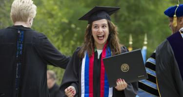 Young woman, in hat and gown with sash, smiling after accepting diploma from President Kington