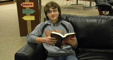 "Grinnell High School senior Nik Lleverino reads a book in the ""The Seven Realms"" series, which was purchased with funds donated by Grinnell College's Pioneer Bookshop."