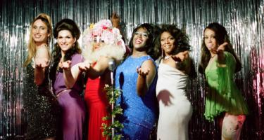 The cast of Happy Birthday, Marsha! in dresses in front of a glitzy backdrop