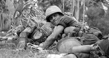 Detail from photograph showing soldiers lying on the ground, with one looking back over his shoulder, lips tense