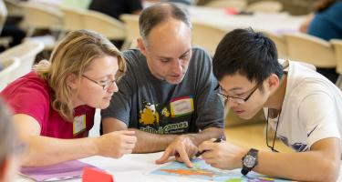 Two host parents and an international student read over a document together