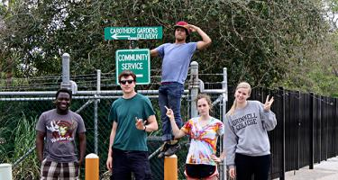 Students posing in front of sign saying Carothers Gardens Delivery and Community Service
