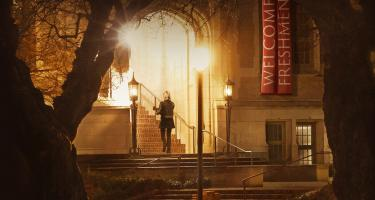 "Young woman walks up stairs under lights on dimly lit campus as ""Welcome Freshman"" banners hang nearby."