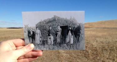 black and white photo of homestead and people held up before a color background of a field
