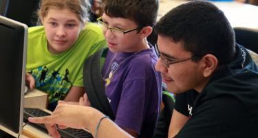 Two young students work with college student mentor on programming challenge