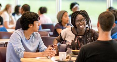 Students talk over dinner in dining hall
