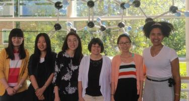 Nicole Snoeberger '09 with professor of chemistry Elaine Marzluff and Marzluff's research students. They are pictured in the 2nd floor atrium of the Noyce Science Center, in front of a chemical structure sculpture that hangs from the ceiling.