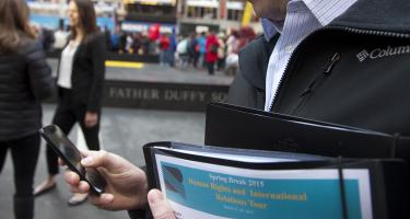 Close up of person checking phone while holding a folder with cover sheet that says Spring Break 2015, Human Rights and International Relations Tour