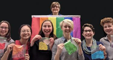 Students in the OSTEM group hold up clear bags with slime of different bright colors. A rainbow flag is behind them.