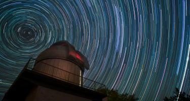 Observatory dome with time lapse image of stars swirling around it