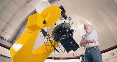 Rrofessor Robert Cadmus with 24-inch reflecting telescope