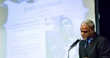 Damani Phillips presenting a lecture with a slide about John Coltrane in the background