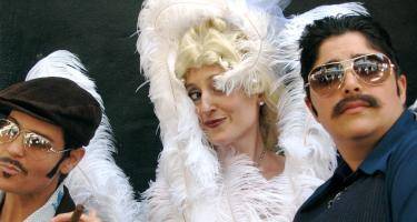 Three people: two blue-suited with mustaches and sunglasses, one with golden curls and large white feathers