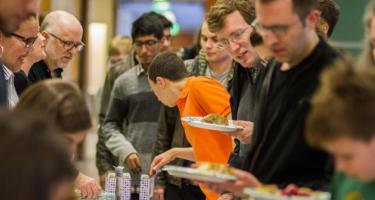 Student in bright orange shirt reaches for silverware, surrounded by line of people