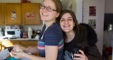 Two women smile at the camera. The one on the right hugs the one on the left, who is holding dough.