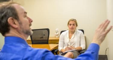Michael Kahn '74 talks with a student during their internship at TIAA