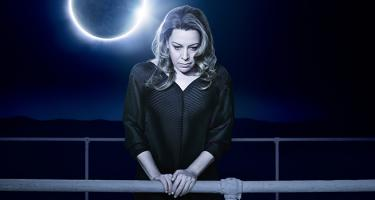 Nina Stemme as Isolde wearing modern dress, standing at a metal bar with solar eclipse in background.