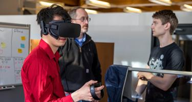 2 students and a staff member work together on a virtual reality system