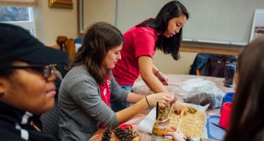 Grinnell College students add peanut butter and bird seed to pinecones