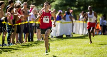Joel Baumann '18 runs for Grinnell in a cross-country race, with fans on the sidelines