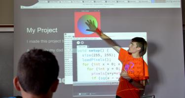 Larsson gestures at a red square with a colored circle on a slide titled My Project, with code displayed below