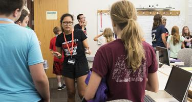 A code camp counselor stands with a group of middle school students
