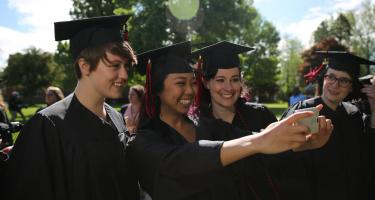 Three graduates in robes taking a selfie before the ceremony