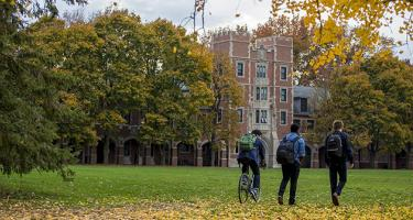three students walk through leaves in front of Gates Tower