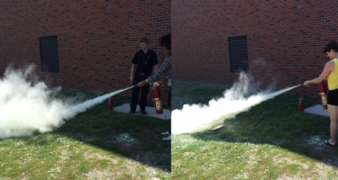 Students discharge fire extinguishers outside during a safety training session before starting their chemistry research projects.